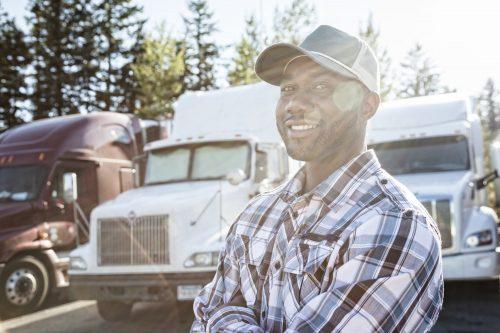 Mörkhyad lastbilschaufför vid sin lastbil på parkering