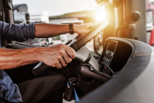 Händer håller i ratt på lastbil