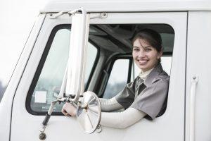 Kvinnlig lastbilschaufför i lastbilsfönstret