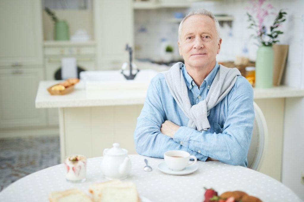 Äldre man sitter vid bordet och dricker kaffe