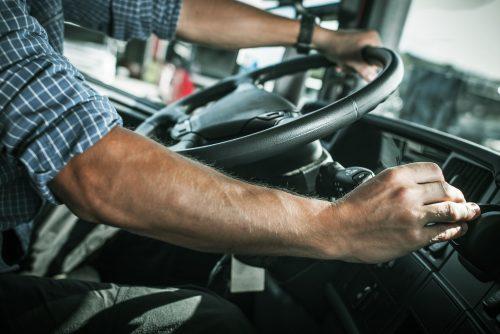 Händerna på en lastbilschaufför i lastbilen