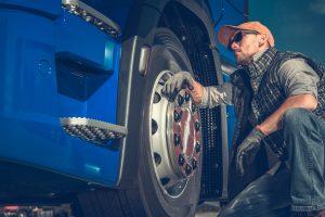 Lastbilschaufför kontrollerar däcken