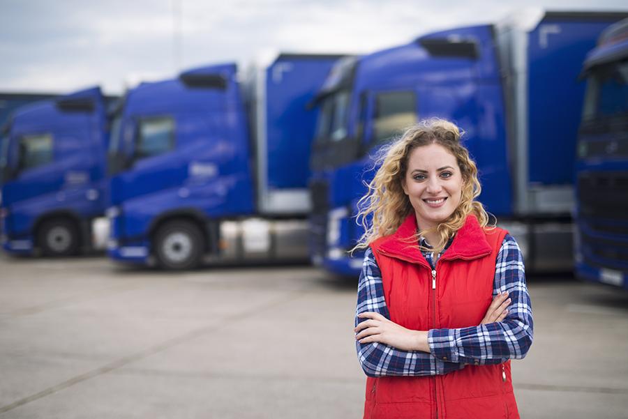 En kvinna framför lastbilar