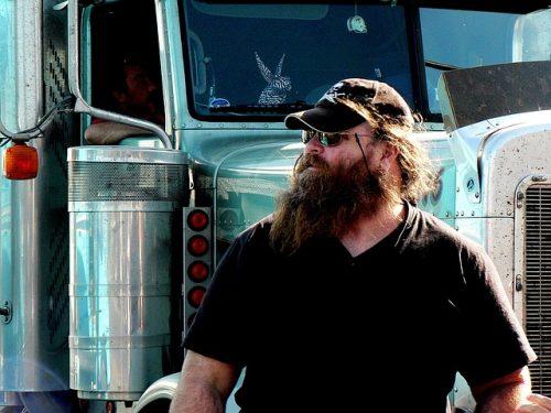 Lastbilschaufför med skägg och keps framför lastbil
